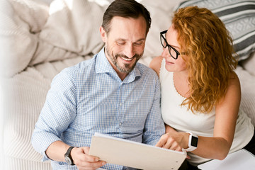 Delighted couple expressing positive emotions at home