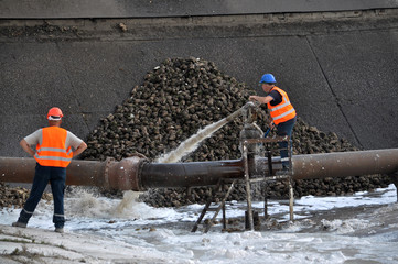 Workers sugar factory with water on piles of sugar beets served raw material for further processing in the shops