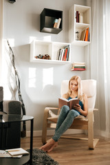 Smiling woman sitting in chair and reading book at home