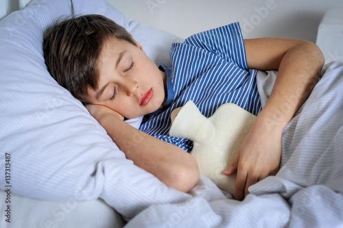 """""""kind schläft mit wärmflasche gegen seine bauchschmerzen"""