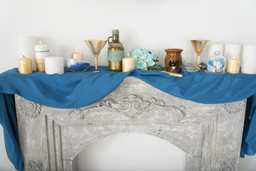 A candle, a mirror on a blue cloth.