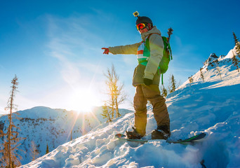 Freeride snowboarder stands on hillside at dawn and shows his hand forward