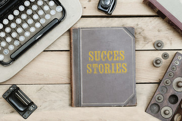 Success Stories on old book cover at office desk with vintage items