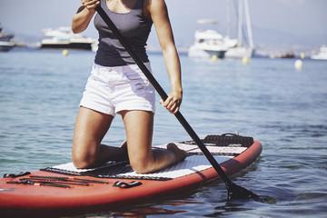 Girl kneeling on a paddle board
