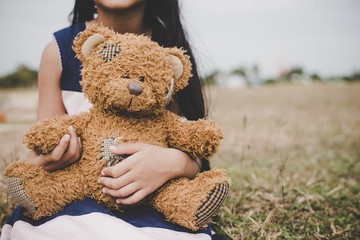 Cute asian girl with teddy bear sitting on meadows field. friendship concept.