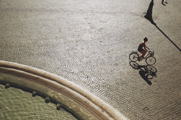 Woman cycling by a fountain
