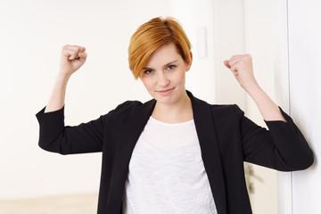 selbstbewusste frau im büro ballt beide fäuste