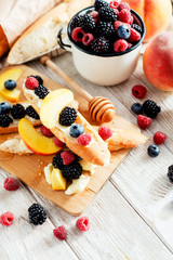sweet snack , bruschetta with berries and fruits , blueberries , raspberries, blackberries and peaches , with butter and honey on wooden background
