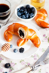 breakfast , sweet bagel with poppy seeds and berries , blackberries and blueberries , honey , black coffee and cream on a wooden background