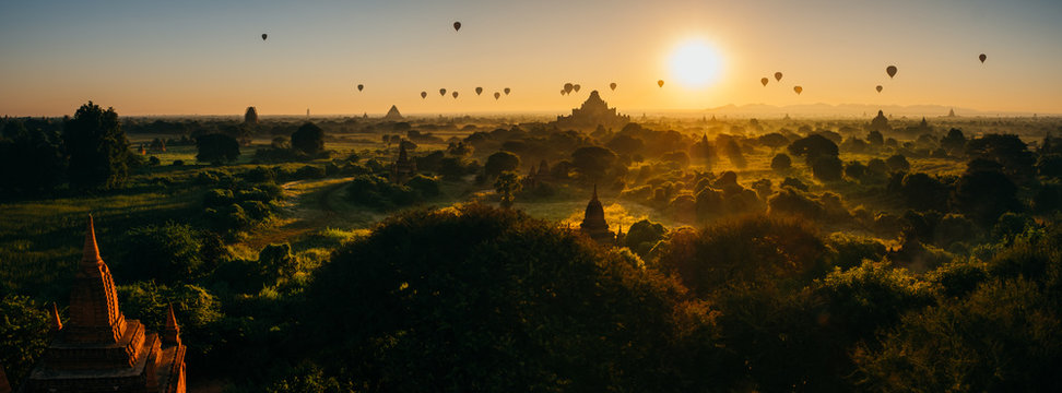 Scenic sunrise with many hot air balloons above Bagan in Myanmar. Bagan is an ancient city with thousands of historic buddhist temples and stupas. panorama, bagan photo