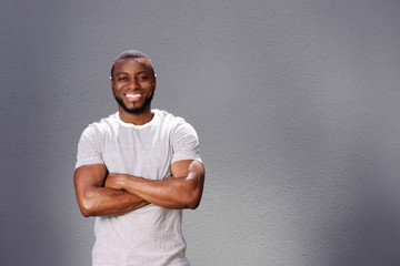 smiling man  standing with arms crossed against gray background