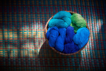 Still life image of colourful cotton in whicker basket. Image made low key.