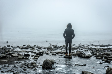 Man in the mist walking on the lake ice in winter afternoon. Peaceful atmosphere. Foggy air.