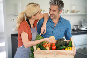 Portrait of couple in domestic kitchen holding basket of fresh vegetables