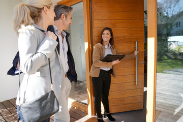 Real estate agent inviting couple to enter house for visit