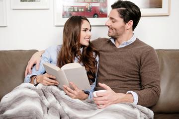Liebespaar kuschelt gemütlich auf der Couch und liest ein Buch