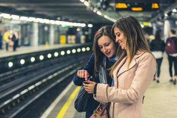 Two girls on the London underground waiting for the train.