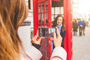Friends taking a picture in a London phone booth