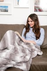 junge Frau kuschelt unter einer Felldecke und liest ein Buch