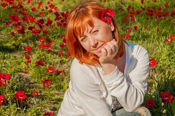 Pretty girl with a red flower behind her ear at the anemone flowering field. Flowering Negev Desert in Israel.