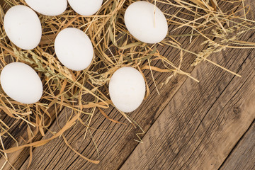 Chicken  eggs in the straw and wooden table.