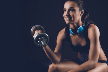 Fitness sporty woman training ,pumping up muscles with dumbbells on black background