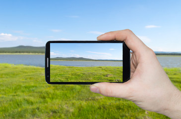 A man hand holding smart phone making photo on smartphone mobile closeup landscape view