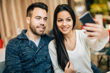 Young couple at cafe taking selfie