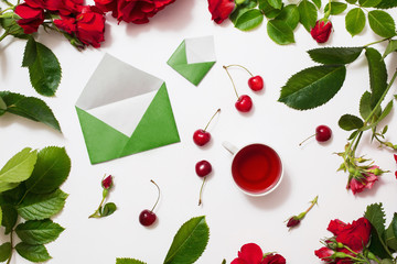 Red tea, ripe cherries, small envelopes with green leaves roses lay on white background. Tea drinking during work. Healing drink. Aromatic morning. Berry compote. Flat lay, top view. Flower frame