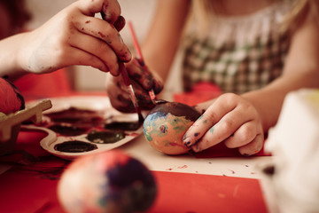 Toddlers having fun painting Easter eggs.