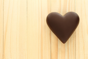 Black chocolate hearts on wooden background