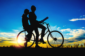 Silhouettes couples and bicycle on sunset sky,couples concept .