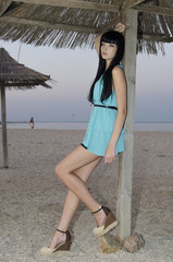 A young attractive girl posing under a thatched roof on the seashore. Summer Resort.