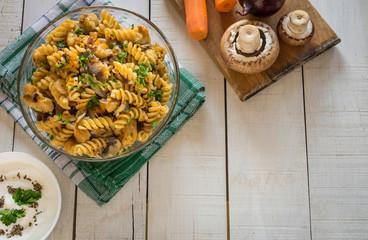 Integral pasta with chicken, mushrooms, vegetables, spices and Greek yogurt. White wooden background.