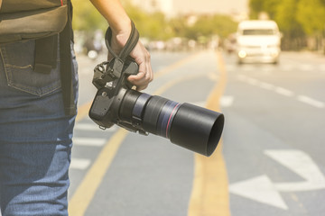 Photographer holding a camera standing on the street in the morning light with blur background  and bokeh.