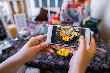 Hands with the phone close-up pictures of food. Breakfast, homemade. girls take food photos on the phone a smartphone, sweet Pancake with fruit.