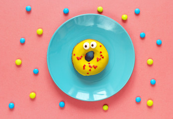 Funny yellow donut with eyes on a blue plate.