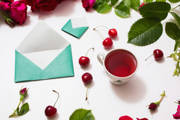 Red Rose tea, ripe cherries, small envelopes with green leaves roses lay on a white background. Tea drinking during work. Healing drink. Send mail. Berry compote. Flower frame. Flat lay, top view, art