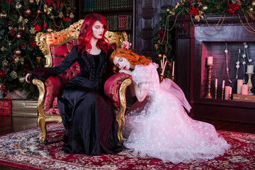Two red-haired girl near the fireplace and the Christmas tree. Fairy and Witch. Christmas story. Boxes with gifts under a fur-tree. Candles in a candlestick. Woman in white and black dresses.