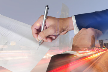 Double exposure of businessman hand holding a pen signing to the document, light trails on the street and urban at dusk, night as business approval concept.