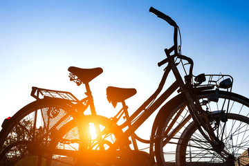 Old rusty bikes silhouette at sunset with blue sky background