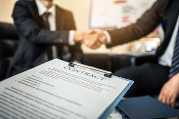Close-up of business contract with pen at workplace on background of office workers interacting. Firm handshake between two colleagues after signing a contract.