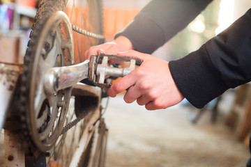 Young man hand repairing his professional bike for another season in garage, preparing