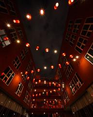 Illuminated lanterns in between buildings at night