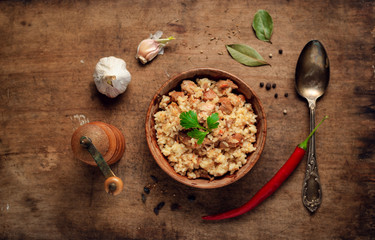 Fresh homemade pilaf - a Middle Eastern or Indian dish of rice cooked in stock with spices, meat, onion and carrot in vintage wooden bowl on a rustic wooden background. copy space. top view