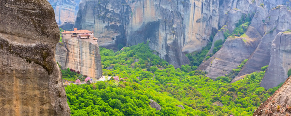 Panoramic view of Meteora monastery on the high cliff rock and road in the mountains at spring...