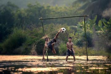children play football on marshland