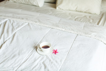 cup of tea and flower on white bed