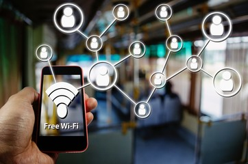 Hand using Smartphone and is using free wifi with icon social media connection concept, Wifi Free on Bus concept on blurred background of people in public transportation bus, color tone effect.