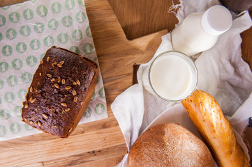 Top view rye bread with sunflower seeds and assortment of breads and glass of milk . Selective focus